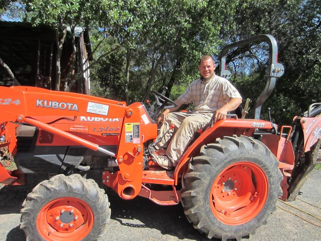 Greg on his tractor ready for clearing, plowing, feeding the pigs, you name it.